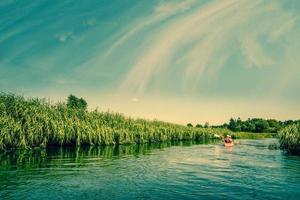 dois homens canoando rio abaixo foto