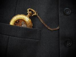 relógio de bolso dourado com colete preto foto