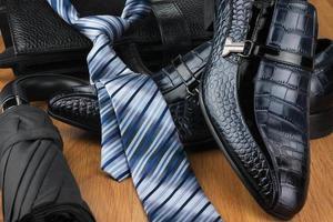 sapatos masculinos clássicos, gravata, guarda-chuva e bolsa na madeira foto