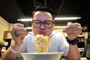 homem comendo macarrão instantâneo foto