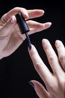 esmalte da mão feminina foto
