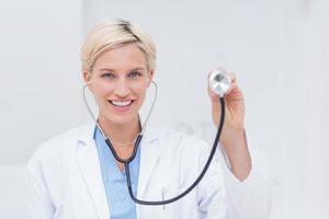 médico feminino confiante segurando o estetoscópio foto