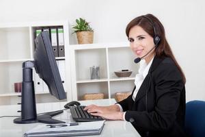 jovem sorridente suporte telefone operador feminino foto