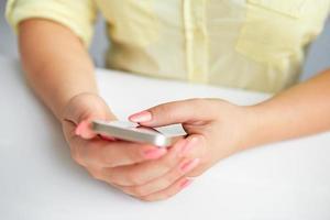 feminino mão segurando um telefone celular foto