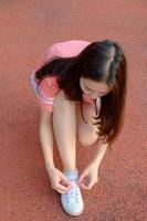 corredor feminino amarrando seus sapatos de desporto foto
