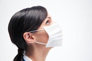 médico feminino em máscara olhando para cima foto