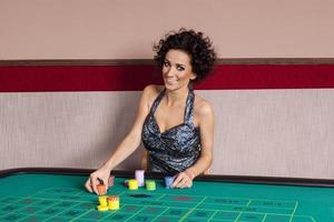 mulher sorridente pela mesa de roleta no cassino