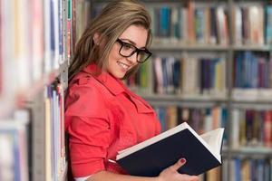 bela aluna em uma biblioteca universitária foto