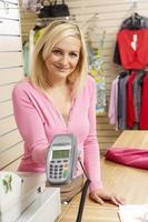 assistente de vendas feminino em loja de roupas foto