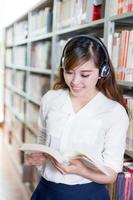 retrato asiático bela aluna na biblioteca foto