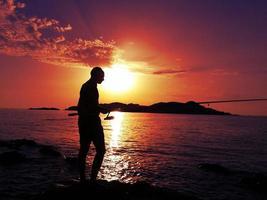 pescador ao pôr do sol