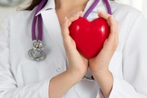 mãos do médico feminino segurando coração vermelho foto