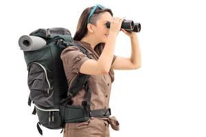 alpinista feminina olhando através de binóculos