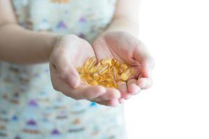 cápsulas de óleo de peixe na mão feminina foto
