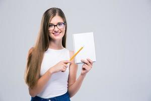 adolescente feminino sorridente, mostrando o caderno em branco foto
