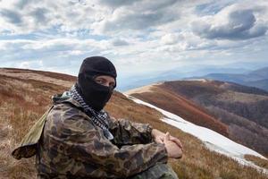homem com o rosto fechado e roupas de camuflagem, sentado na montanha foto