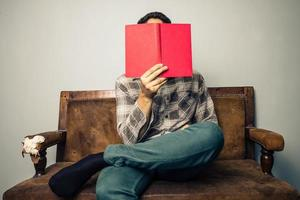 homem, escondendo o rosto atrás de livro no sofá velho foto