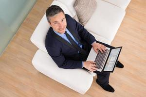 empresário no sofá usando laptop foto