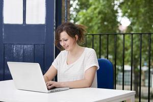feliz jovem empresária trabalhando no laptop na mesa foto