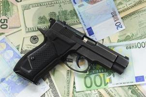 dinheiro como pano de fundo e uma arma foto