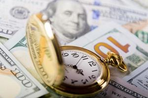 relógio de ouro e notas de cem dólares