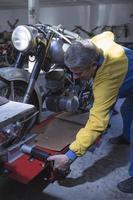 homem ajustando uma moto foto
