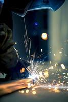 soldador, trabalhando com ferro. faíscas e máscara. foto