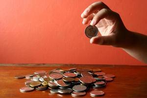 mão pegando uma moeda de um monte de troco foto