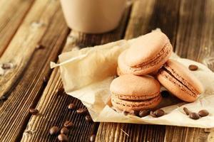 macarons de café com grãos de café sobre fundo marrom de madeira foto