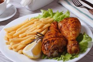 coxinhas de frango frito com batata frita, alecrim e limão foto