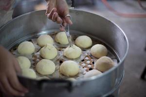 pães cozidos no vapor sendo cortados, prontos para cozinhar. chinatown, bangkok. foto