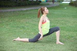 jovem bonita fazendo exercícios físicos no gramado foto