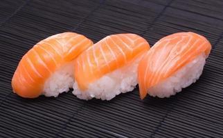 salmão sushi na cor de bambu de madeira preto foto