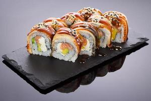 sushi de enguia em um prato de pedra sobre fundo preto foto