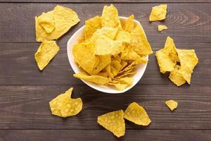 chips de nachos em fundo de madeira. vista do topo foto