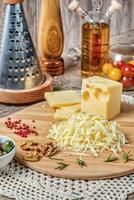 queijo gouda ralado em um ralador deitado sobre uma prancha foto