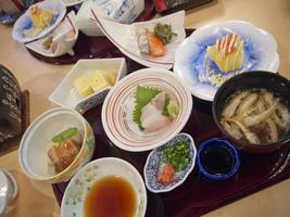 refeições tradicionais do café da manhã japonês com sashimi de peixe frito e tofu servido na bandeja foto