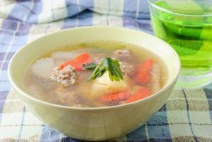 sopa clara com coalhada de feijão e carne de porco picada foto