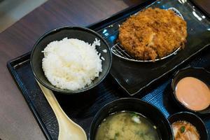 carne de porco frita e arroz japonês no conjunto bento foto