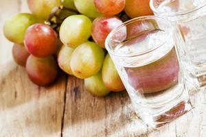 grappa em um copo pequeno e uvas maduras