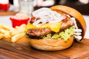 hambúrguer de porco com queijo, vegetais e servido com batatas fritas
