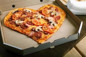 forma de coração de pizza na vista superior do fundo escuro de madeira