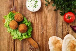 bolas de falafel de grão de bico em uma mesa de madeira com legumes foto