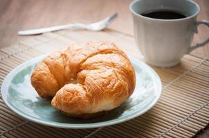 café da manhã com croissants, xícara de café preto foto