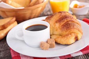 xícara de café, croissant e suco de laranja foto