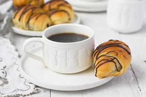 rolos de massa folhada com xícara de chocolate e café foto