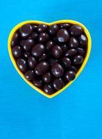 tigela em forma de coração cheia de bagas cobertas de chocolate foto