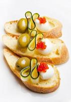 bruschetta com mussarela, azeitonas verdes, abobrinha e caviar vermelho