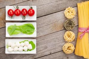 folhas de tomate, mussarela, macarrão e salada verde foto