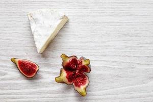 pedaço de camember com figo splittef na mesa de madeira branca foto